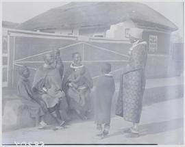 Pretoria district, 1952. Ndebele women and children sitting on bench in kraal.