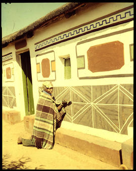 Pretoria district. Ndebele woman decorating traditional home.