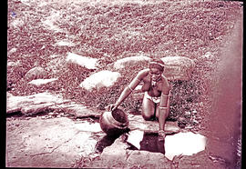 """Eshowe district, 1929. Zulu girl collecting water from puddle."""