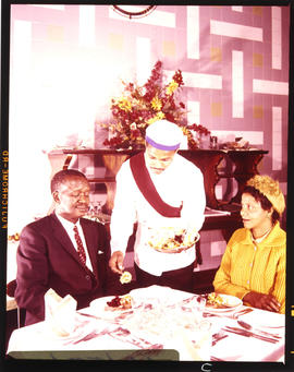 Group of black people being served in dining room.