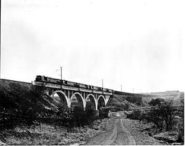 Vryheid district, 1978. SAR Class 34-600 heading five other locomotives and goods train over bridge.