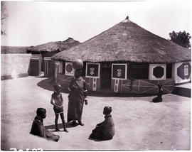 Pretoria district, 1952. Ndebele kraal, family at decorated wall and gate.