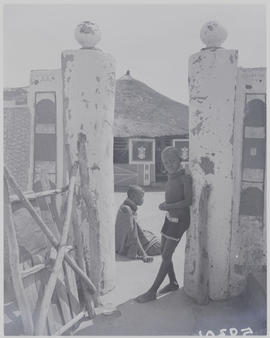 Pretoria district, 1952. Ndebele kraal, young boy leaning on wall.