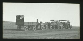 Two tented wagons drawn by steam tractor.