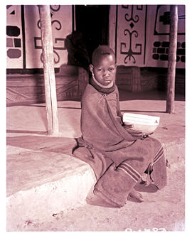 """1951. Young Ndebele child with bowl in front of hut."""