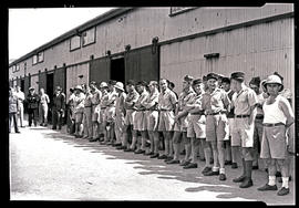 Soldiers in front of large hangar.
