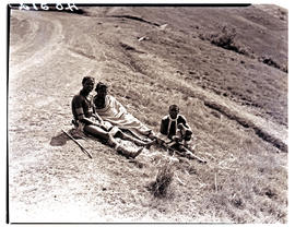 Transkei, 1940. Three people sitting at roadside.