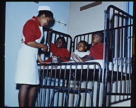 Nurse with three children at hospital bed.