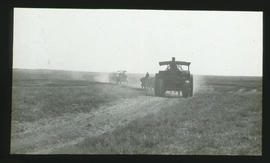 Tractors on dusty road.