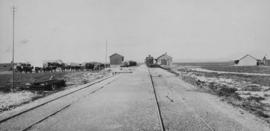 Houtkraal, 1895. Cape 3rd Class on train with station and inspanned oxen in the distance, looking...